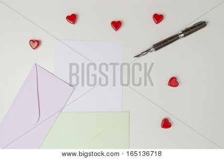 Envelopes, message, pen and small red hearts on white table. Top view. Love letter, valentines day concept