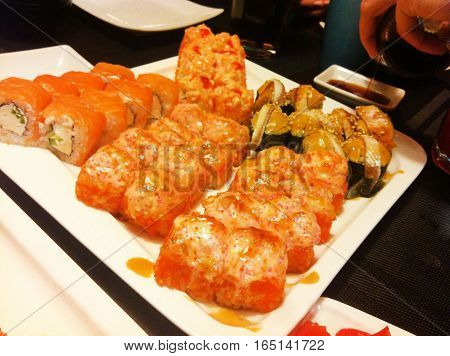Set of sushi maki rolls with salmon fish, eel, avocado, cream cheese baked sushi with soy sauce wasabi and ginger served on white plate wooden table background Traditional Asian cuisine tasty food served at Japanese restaurant