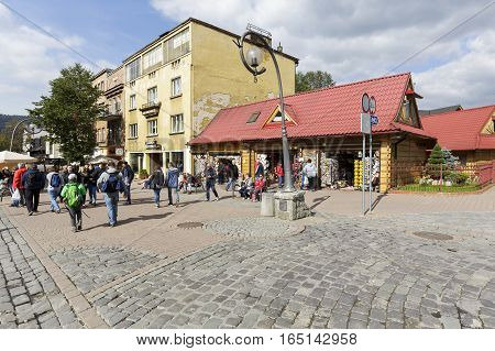 ZAKOPANE POLAND - SEPTEMBER 23 2016: People are walking along the street Krupowki that is a frequently visited place by tourists coming to town. Many tourist attractions are located there.