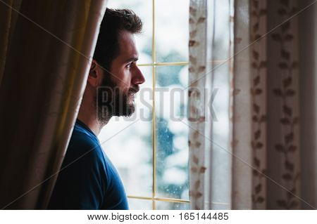 Young sad mad standing by the window looking outside