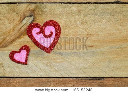 Red and pink glitter, sparkle and twinkle hearts set on pallet wood background.  Valentine's Day, Wedding, Anniversary, romantic symbol of love.