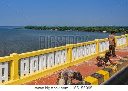 Goa, India - November 13, 2012: Repair work on the bridge across Zuari River largest river in the state of Goa, India. Construction workers painting curb.