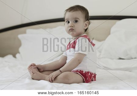 Portrait of a beautiful baby girl sitting on bed after a day dream