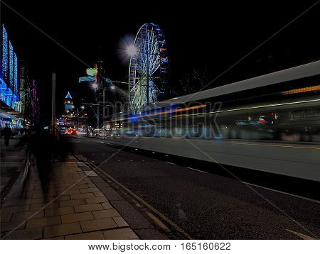 Evening street in Edinburgh. Edinburgh, Scotland - December 19, 2016 Tram traffic, carousels and people on one of the main streets of Edinburgh.