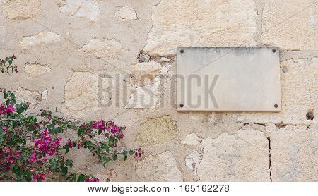wall of stone with an empty plaque and some flowers at left corner