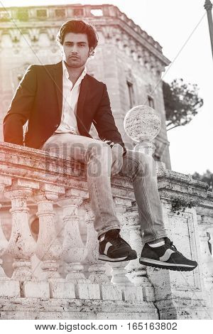 Young stylish man model sitting on old historic low wall. Intense light. Black and white with a light color.