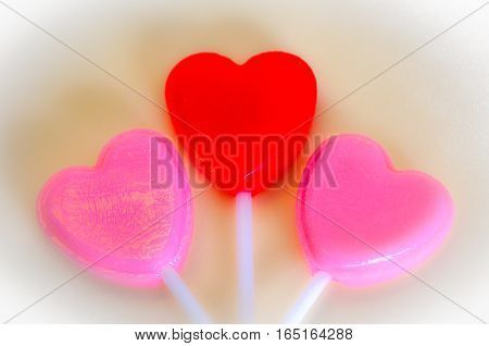 Pink and red hearts resting on silk backdrop.  Valentine's day, wedding, anniversary, romantic symbol of love.