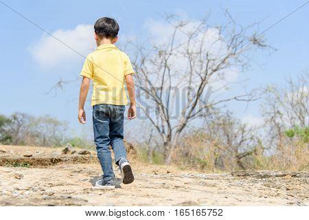 Boy Walking On The Rocky Land.