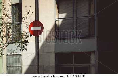 Red stop sign in Barcelona in front of facade of residential house with latticed windows and diagonal shadow branches of tree on the left