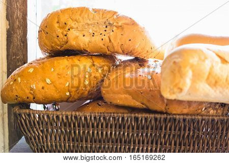 fresh bread buns in a basket on a wooden table