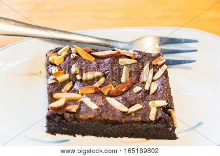 almond chocolate brownie cake on white dish and fork