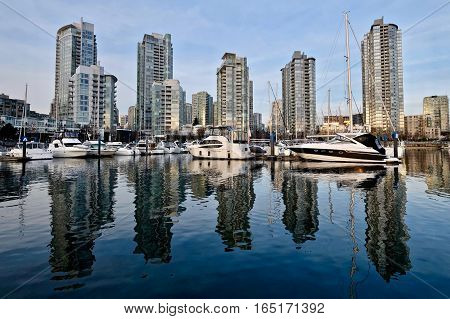 City buildings and boats reflection in water. Yaletown. False Creek. Vancouver downtown. British Columbia. Canada.