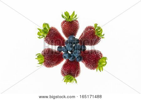 strawberries and blueberries arranged in circle on white background