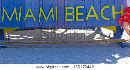 Miami Beach sign on a sandy beach in Florida USA. The beach famous stop for a memorable picture.