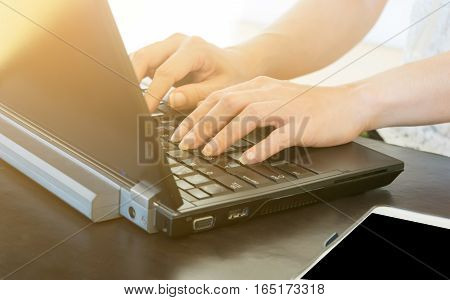Young office Woman typing laptop computer on the desk.