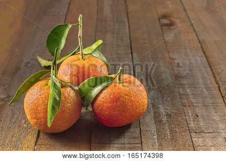 A photo of vibrant orange tangerines with green leaves on a dark wooden boards texture with copyspace