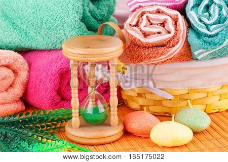 Spa set with colorful towels candles and sandglass on bamboo background.