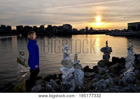 Woman watching sunset in city harbor. City Gate. Chinatown. False Creek. Vancouver downtown. British Columbia. Canada.