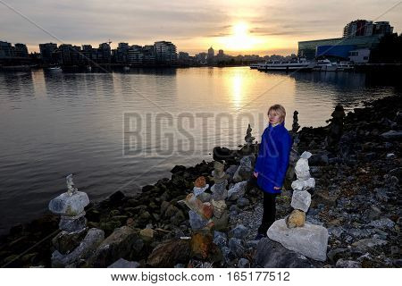Woman watching sunset in city harbour. City Gate. Chinatown. False Creek. Vancouver downtown. British Columbia. Canada.