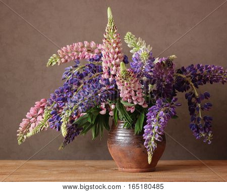 Still life with lupins on the table in rustic style.