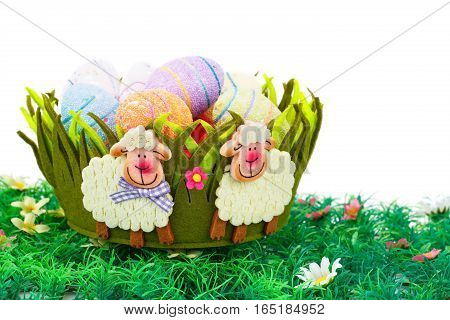Easter decoration with colorful eggs in basket on artificial grass.