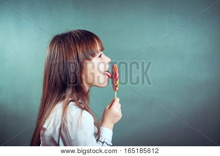 6 or 7 years old child girl eating big multicolor spiral lollipop candy