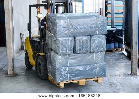 Electric forklift carries boxes. Cargo packed in polyethylene film gray.