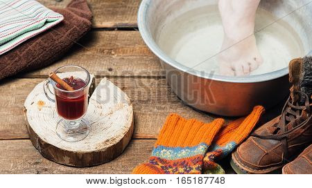 Footbath closeup. Bare foot in basin with warm water,  glass of mulled wine, boots and wool socks on the floor