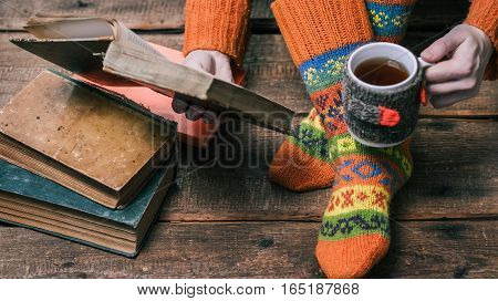 Female feet in warm winter socks on the wooden floor and hands with book and mug of tea. Selective focus