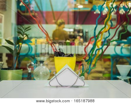Picture of the white napkin in napkin holder. Napkin holder and yellow cup on the table in the cafe room. Tableware against the blurred background of the cafe room with multicolour decoration.