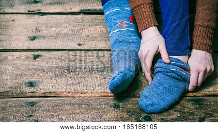 Female feet and hands putting on warm winter sock on the wooden floor. Closeup view