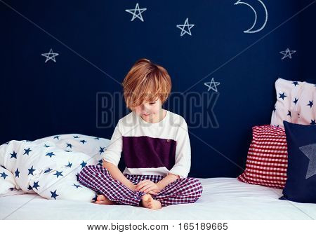 Cute Smiling Kid In Pajamas Sitting In Bed