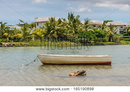 Boat on the river with villas in the background Tamarin Black River District Mauritius