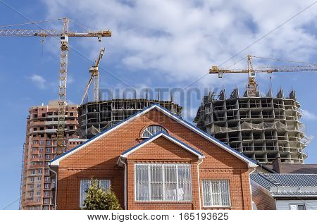 Brown house on a background of new buildings and tower cranes