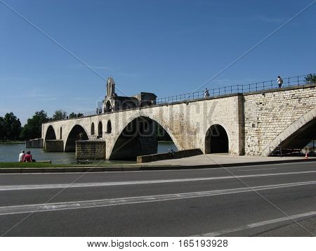 Medieval stone Benezet bridge admire by sitting couple in french historical city of AVIGNON with desolate road in FRANCE and clear blue sky in warm sunny summer day, PROVENCE, EUROPE, JUNE