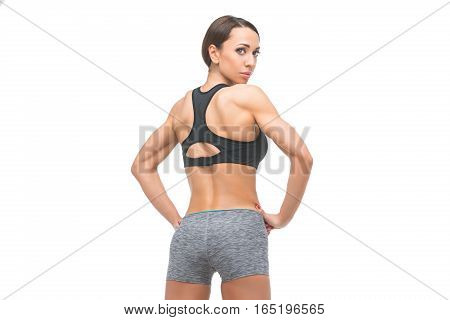 Beautiful fit muscular young woman in sport bra and shorts isolated on white background. Perfect body. Studio shot. Copy space.
