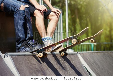 Couple of teenagers with boards sitting on top of mini-ramp in a skatepark ready to roll-in and do tricks