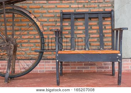 Wooden chairs on orange brick walls and old bicycles.