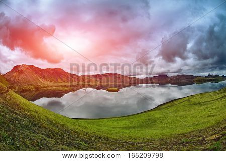 Lake coast with mountain reflection at the cloudy day, Iceland