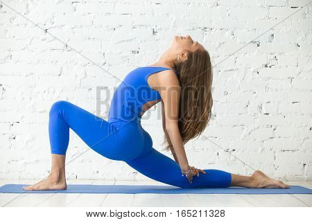 Young attractive woman practicing yoga, standing in Horse rider exercise, anjaneyasana pose, working out, wearing sportswear, blue jumpsuit, indoor full length, white loft studio background