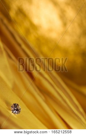 Beautiful big diamond jewelry on golden satin cloth background. Fine natural precious stone