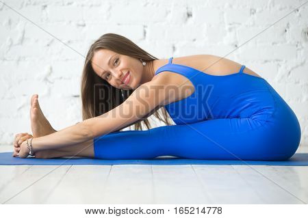 Young happy woman practicing yoga, sitting in Seated forward bend exercise, paschimottanasana pose, working out, wearing sportswear, blue suit, indoor full length, white studio, looking at the camera