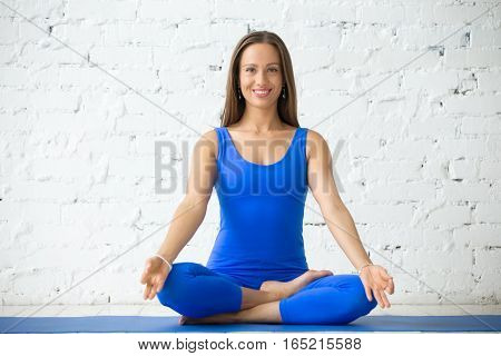 Young smiling woman practicing yoga, sitting in Half Lotus exercise, Ardha Padmasana pose, mudra, working out, wearing sportswear, blue suit, indoor full length, white studio, looking at the camera