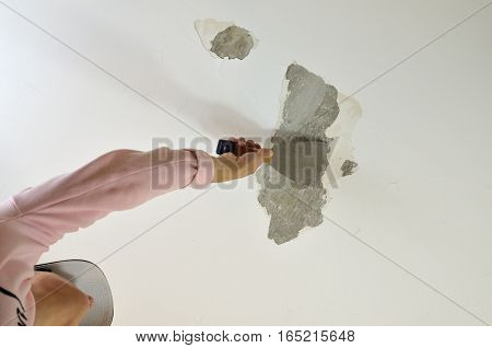 Woman holding a plaster spatula peeling a ceiling preparing it for smoothing