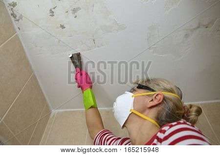 Woman with protecting equipment holding a plaster spatula peeling a ceiling preparing it for smoothing
