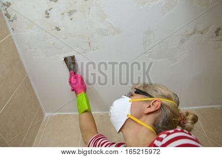 Woman with protecting mask holding a plaster spatula peeling a ceiling preparing it for smoothing
