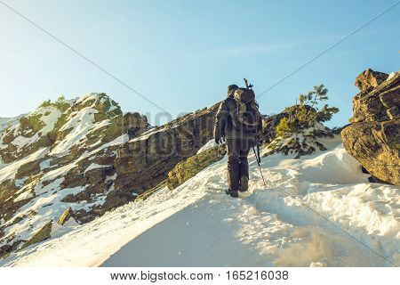 Hikers Traveling On Snowy Mountains To The Top At Sunset