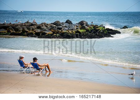 BELMAR NEW JERSEY-AUGUST 1- Two young women enjoy a peaceful beach day along the shoreline on August 1 2015 in Belmar New Jersey.