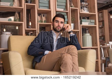 Young Adult Man Listening Phone Sitting Indoors Cafe Interior