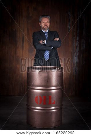 Mature businessman in a black suit and barrel of crude oil on dark background